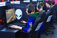 Young gamers in headphones playing at the computer. Moscow, Russia, April, 2018: Young gamers in headphones playing at the computer on a e-sport tournament Royalty Free Stock Images