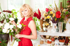Young gardener. In a flower shop, holding flowers and smiling Royalty Free Stock Photos