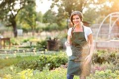 Young gardener in green apron sprinkling plants, garden Stock Images