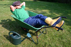 Young gardener having a break. Boy relaxing in his wheelbarrow Royalty Free Stock Images
