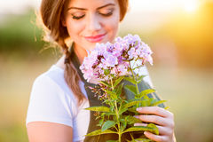 Young gardener in her garden holding flowers, sunny nature Royalty Free Stock Image