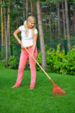 Young gardening woman with rakes. Outdoor. view on trees Stock Photography