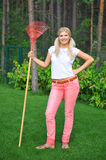 Young gardening woman with rakes. Young  pretty gardening woman with red rakes. outdoor in her garden Royalty Free Stock Images