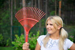 Young gardening woman with rakes. Young  pretty gardening woman with red rakes. outdoor in her garden Stock Image