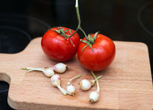 Young garlic and a couple tomatoes. On the board Stock Photo