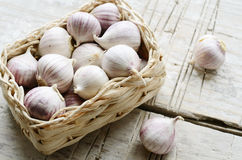 Young garlic in small wattled basket on wooden backround Royalty Free Stock Photos