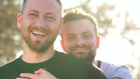 Young gay couple having fun at sunset outdoors. Attractive young gay couple having fun at sunset outdoors stock video footage