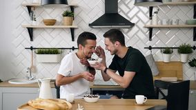 Young gay couple are sitting at the table and having breakfast in the morning at kitchen. Handsome young guy is feeding. His partner sitting at the table in the stock footage