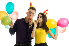Young gay guy and girl celebrates birthday with balloons and blow horns Royalty Free Stock Photo