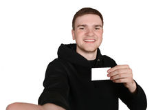 Young gay guy makes self with a blank card in his hand. Royalty Free Stock Image
