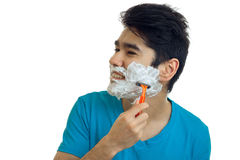 Young gay guy turned his head to the side and shaves his beard with foam Royalty Free Stock Image