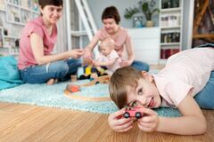 A young gay lesbian family with two children, a son and a daughter, spend time at home. They sit on the floor and play