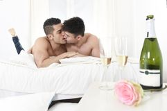 Young gay men couple kissing on bed with rose after champagne toast celebrating valentines day in homosexual love concept Stock Photos