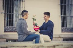 Young  gay men couple with rose and box present celebrating valentines day in love Royalty Free Stock Photos