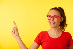 Young geek woman in red t shirt point in copy space over vibrant. Yellow background stock photo