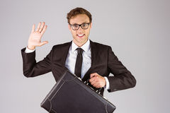 Young geeky businessman holding briefcase Royalty Free Stock Photos