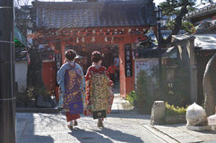 Young geisha walking through Kyoto. Two young Geisha dressed in elaborate Kimono walk past the entrance of a small local shrine in western Kyoto stock photos
