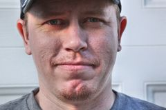 Young Generation X face of man wearing baseball ca. P, smiling with lips closed Stock Images