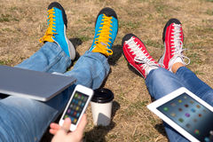 Young Generation People Using Gadgets In Park Stock Photo