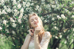 Young gentle blonde woman in blooming garden. Girl enjoying the fragrance of spring. She clothed white lacy dress Stock Photography
