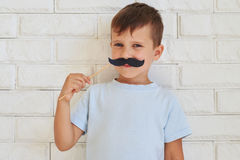 Young gentleman holding paper moustache with rather shrewd look Royalty Free Stock Photos