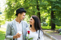 Young gentleman presenting a rose to his love in the park Royalty Free Stock Photo