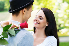 Young gentleman presenting a rose to his love in the park Royalty Free Stock Images