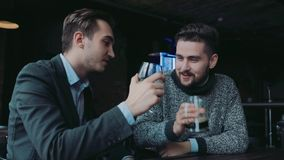 Young gentlemen having fun in the pub, talking actively and toasting. Man's club, male traditions. Active lifestyle. Young gentlemen having fun in the stock video footage