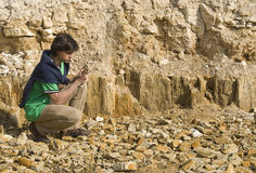 Young geologist studying rock type Royalty Free Stock Photo