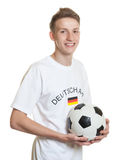 Young german soccer fan with ball and blond hair Royalty Free Stock Photo