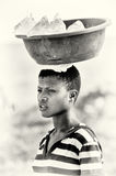 Young Ghanaian woman carries a basin with cold wa Royalty Free Stock Photo