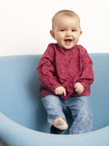 Young giggling baby dancing. Smiling baby girl dancing on a seat Stock Image