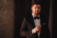 Young ginger bearded man holding a vintage glass with red wine against the light, black on background. look at the. Camera Royalty Free Stock Photo