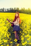 Young ginger hair girl in 70s style with acoustic guitar. In rapeseed field royalty free stock photos