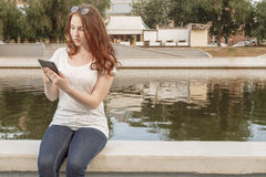 Young gingerish woman work with tablet pad in park Royalty Free Stock Photography