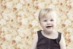 Young gir smiling against floral background Stock Photography