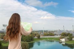 Young girk tourist with map sightseeing View on Olympiapark with. Olympic tower at Munich, Bavaria, Germany Royalty Free Stock Photos