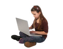 Young girl 10. Young girl sitting with her legs crossed with a laptop computer in her lap Royalty Free Stock Image