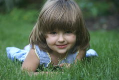 Young girl. A three years old girl laying down on the grass Royalty Free Stock Photography