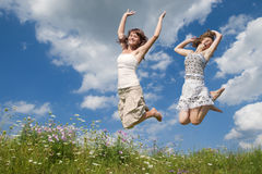 Young girl. Jumping in field with flowers Stock Images
