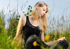 Young girl. Beautiful young girl sitting and listening music outside with sky and grass in background Royalty Free Stock Images