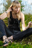 Young girl. Beautiful young girl sitting and listening music outside with sky and grass in background Royalty Free Stock Photography