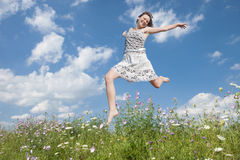 Young girl. Jumping in field with flowers Stock Photography