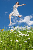 Young girl. Jumping in field with flowers Royalty Free Stock Photography