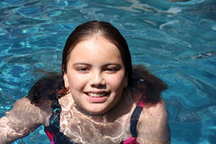 Young girl (12) smiling in pool. A 12-year-old brown-haired girl rests her arm on the edge of a blue swimming pool. She has a pleasant smile Royalty Free Stock Photo