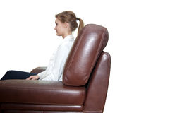 Young girl. Sitting in a leather armchair Royalty Free Stock Photo