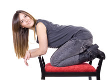 Young girl. A young beautiful woman on a red chair Stock Photography