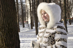 The young girl. Rejoices to the sun in the winter in a white fur coat with a fluffy hood Royalty Free Stock Photography