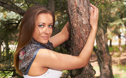 Young girl. In a white T-shirt hugging a tree Stock Images