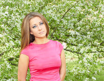 Young girl. Girl in a pink dress on a background of flowering tree Royalty Free Stock Photo